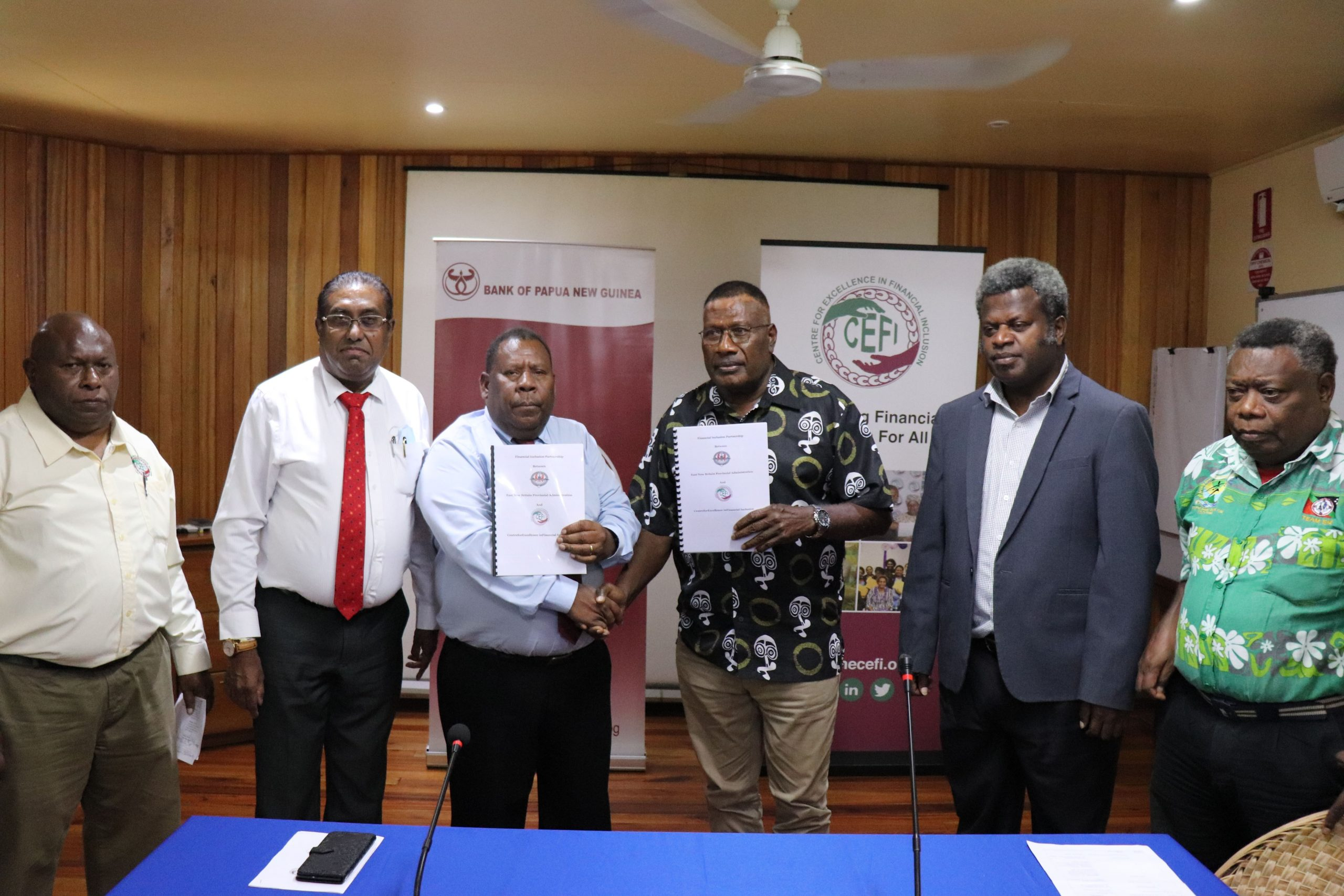 Assistant Governor, Financial System Stability Group, Bank of PNG – Ellison Pidik (3rd from left) and East New Britain Governor Nakikus Konga (3rd from left) shake hands to confirm financial inclusion partnership between CEFI and East New Britain Province.