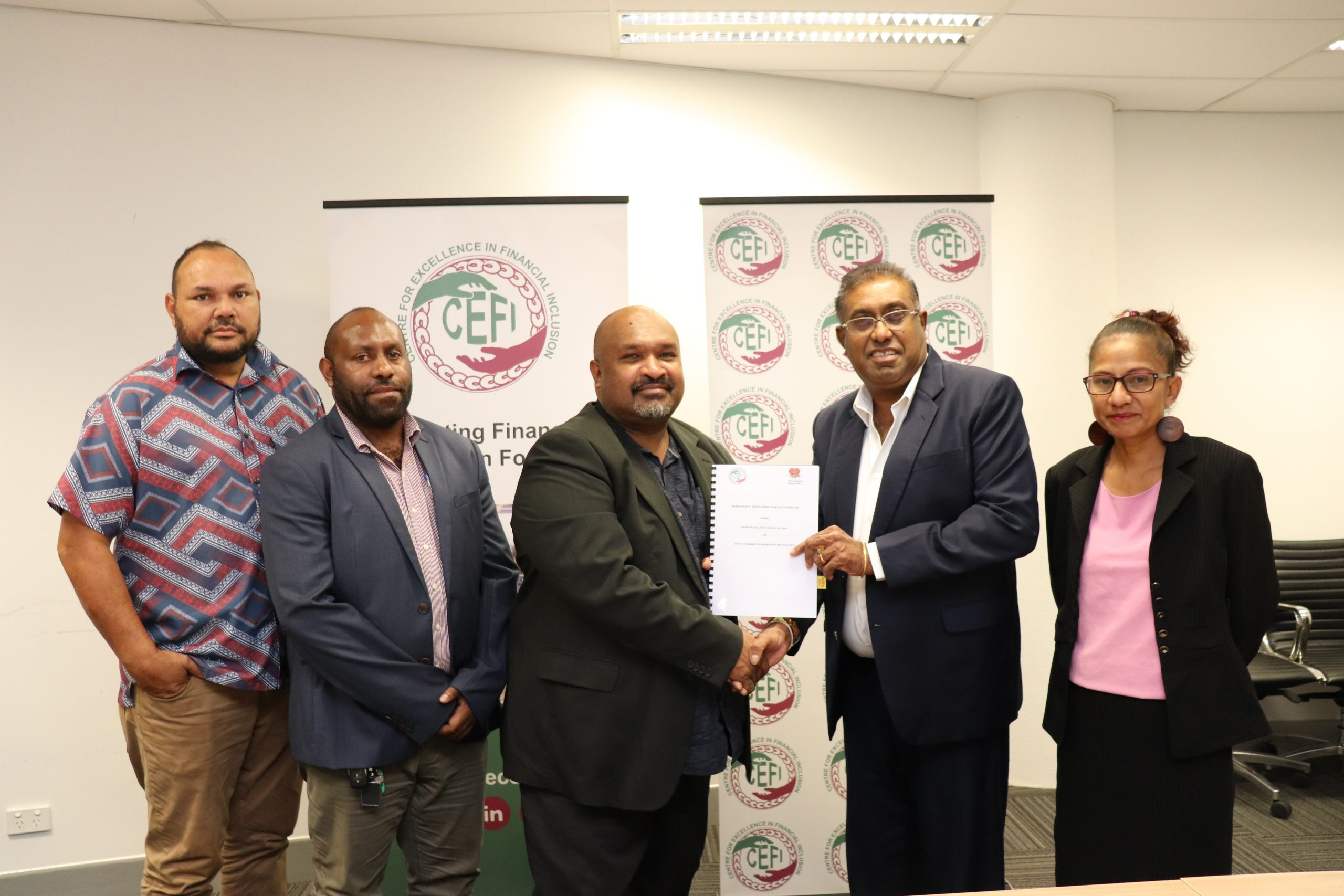 Member for Port Moresby North West LOhia Boe Samuel (left) and CEFI Executive Director Saliya Ranasinghe shaking hands to confirm both parties partnership in working together to deliver financial inclusion activities in the Port Moresby North West Electorate.